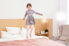 Cheerful girl jumping on bed. I am inspired. Exuberant little girl smiling and having fun at home Royalty Free Stock Images