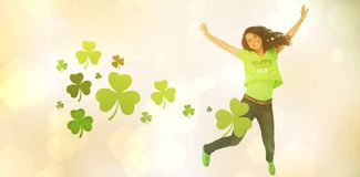 Cheerful girl jumping while celebrating st patricks day. Against white background Stock Photos