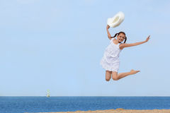 Cheerful girl jumping over the water at the beach Royalty Free Stock Photos