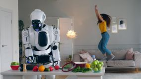 Cheerful girl jumps on a couch while a robot cooks dinner. 4K stock video footage