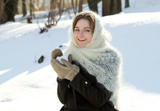 Cheerful girl in a knitted scarf winter throws snow Russian winter Royalty Free Stock Photography
