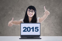 Cheerful girl with laptop showing thumbs-up Stock Photos