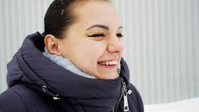 Cheerful girl laughs, tongue catches snowflakes under snow.  stock footage