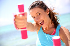 Cheerful girl lifting weights Stock Image