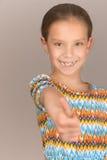 Cheerful girl lifts thumb upwards Stock Photography