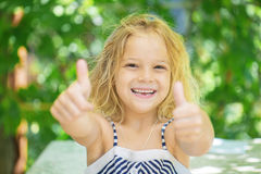 Cheerful girl lifts thumb upwards Stock Images