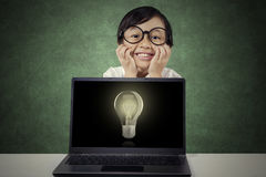 Cheerful girl with lightbulb on laptop Royalty Free Stock Images