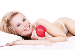 Beautiful blonde girl lying on the bed, holding apple. Stock Images