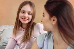 Cheerful girl listening to her best friend stock images