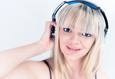 Cheerful girl listening to music with blue headphone Royalty Free Stock Image