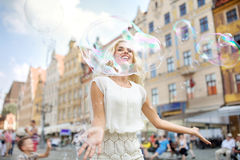 Cheerful girl looking through the huge bubble Royalty Free Stock Photos