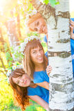 Cheerful girl looks out from behind  birch trunk Royalty Free Stock Photography