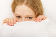 Cheerful girl looks out from under the blanket stock images
