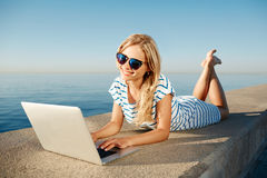 Cheerful girl lying on the beach and talks to her friends on the Stock Image