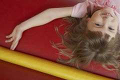 Cheerful Girl Lying In Bouncy Castle Royalty Free Stock Photos