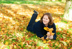Cheerful girl lying on the ground in park Royalty Free Stock Photo