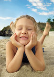 Cheerful girl lying on a sandy beach and laughing, Royalty Free Stock Photo