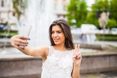 Cheerful girl making selfe photo and showing victory Stock Image