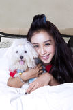 Cheerful girl and maltese dog in the bedroom. Picture of beautiful young woman embracing a maltese dog on the bed and smiling at the camera Royalty Free Stock Photography
