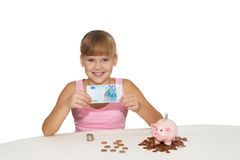 Cheerful  girl with money in hands isolated. Cheerful girl with money in hands and piggy  bank on  table isolated Royalty Free Stock Photos