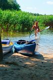Boats at the dock, cheerful girl with oars in his hands. Cheerful girl with oars in his hands, boats at the dock Stock Photos