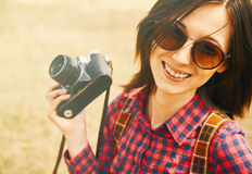 Cheerful girl with old photo camera in spring. Cheerful hipster girl holding vintage old photo camera in spring outdoor Royalty Free Stock Photo