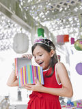 Cheerful Girl Opening Birthday Present At Party Stock Photography