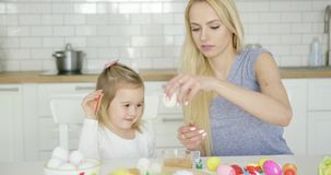 Cheerful girl painting eggs with mother stock footage