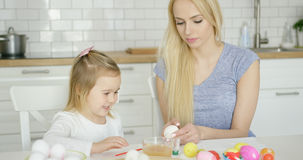Cheerful girl painting eggs with mother Royalty Free Stock Photos