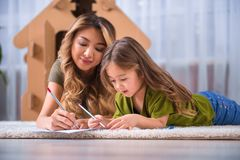 Happy mother and child drawing picture on flooring Royalty Free Stock Photo