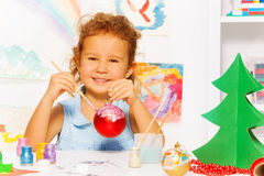 Cheerful girl painting New Year while sitting. Alone at the white table with decorations on it and carton green Xmas tree nearby Royalty Free Stock Photo