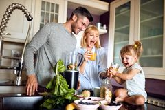 Cheerful girl with parents in kitchen royalty free stock image