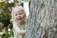 Cheerful Girl Peeking From Behind Tree Stock Photo