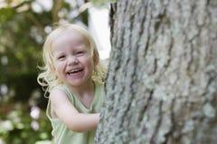 Cheerful Girl Peeking From Behind Tree. Portrait of a cheerful little girl peeking from behind tree Stock Photo