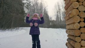 Cheerful girl peeping out from trees in winter forest playing hide and seek. Cheerful girl peeping out from trees in winter forest while playing hide and seek stock footage