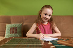 Cheerful girl in pink dress drawing pencils Royalty Free Stock Images
