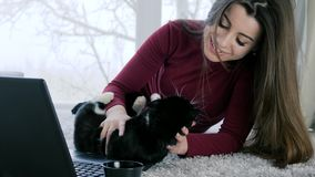 Cheerful girl is played with cat lying on floor near laptop in holiday on background of large window. Cheerful girl is played with cat lying on floor near laptop stock video footage