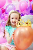 Cheerful girl playfully put crown on balloon Stock Photo