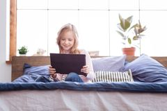 Cheerful girl playing games on her tablet royalty free stock photography