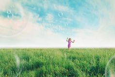 Cheerful girl playing among soap bubbles in summer royalty free stock photo