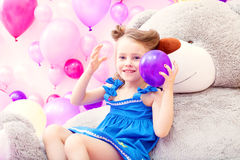 Cheerful girl plays with balloon in playroom Stock Image