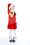 Cheerful girl in a polka dot dress and hat of Santa Claus Stock Images