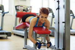 Cheerful girl posing exercising on bench in gym Royalty Free Stock Photo