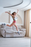 Cheerful girl posing during jump in living room Stock Photos
