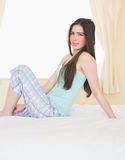 Cheerful girl posing and looking at camera sitting on her bed Stock Photo