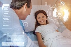 Optimistic ill girl smiling to her father while staying in bed stock photography