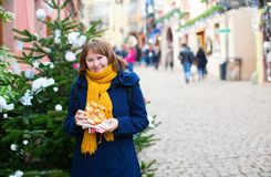 Cheerful girl with pretzel on Christmas market Stock Photo