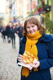 Cheerful girl with pretzel on Christmas market Stock Photos