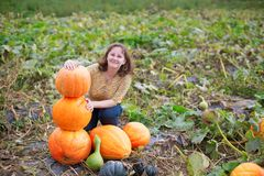 Cheerful girl on a pumpkin patch at fall Stock Images