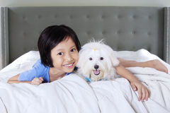 Cheerful girl and puppy in the bedroom. Attractive little girl lying in the bedroom with a maltese dog and smiling at the camera Royalty Free Stock Images
